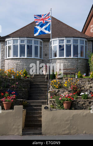 United Kingdom flags. The Union Jack and Scottish Saltire fly above a bungalow in England during the 2014 Scottish independence referendum campaign.