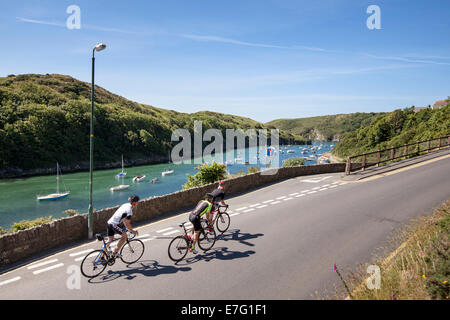 Three cyclists ride along a road by the harbour in Pembrokeshire, Wales - Stock Photo