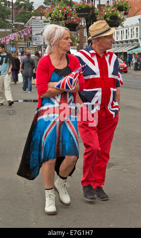 Elderly couple dressed in bright and unusual clothes made from Union Jack British flag and carrying flag at Whitby - Stock Photo