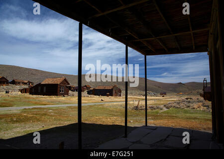 Old buildings seen from under the verandah of the Wheaten and Hollis Hotel, Bodie Ghost Town, Eastern Sierra, California, - Stock Photo