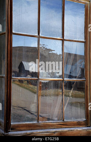 Reflection in window of Wheaten and Hollis Hotel, Bodie Ghost Town, Eastern Sierra, California, USA - Stock Photo