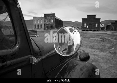 Derelict vintage truck and Bodie Post Office, IOOF Hall, and Miner's Union hall , Bodie Ghost Town, California, - Stock Photo