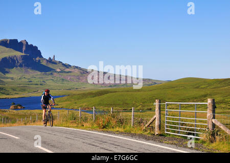 Cyclist on a road at The Storr with the The Old Man of Storr pinnacle, Trotternish Peninsula, Ross, Skye and Lochaber - Stock Photo