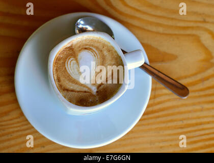 Cup of cappuccino with milk foam in a heart shape - Stock Photo