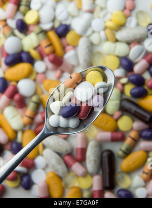 Tablets and pills on a table and on a spoon, 18 August 2014 in Hamburg. - Stock Photo
