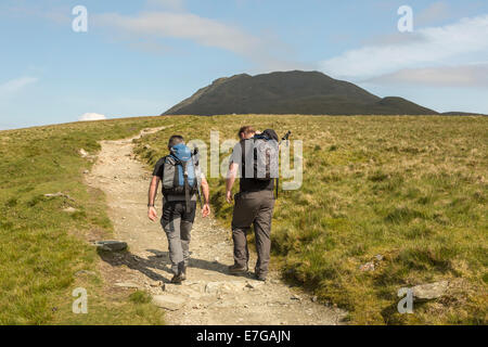 Two male hill walkers walk up the stone path leading to the summit/peak of Ben Lomond - Stock Photo
