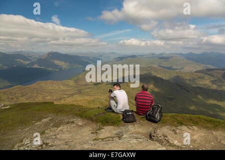 Two men glance over the vast hills of Scotland on top of Ben Lomond. - Stock Photo