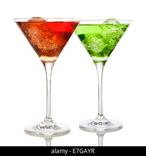 Red and green drinks on the rocks in martini glasses on white background - Stock Photo