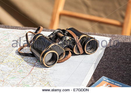 Old fashioned pair of binoculars placed on top of a map - Stock Photo