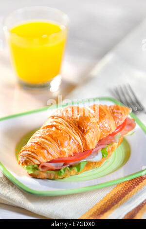 croissant with salad, ham and tomatoes - Stock Photo