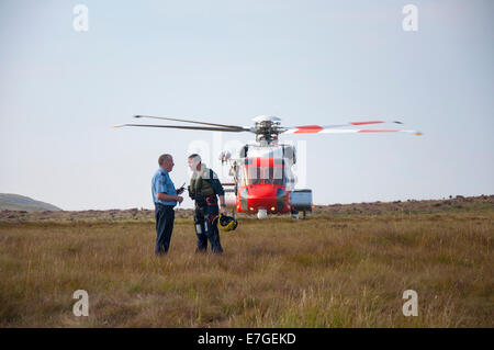 Irish Coast Guard IRCG  Garda Cósta na hÉireann Sikorsky helicopter crew member liases with Irish policeman - Stock Photo