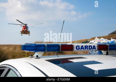 Irish Coast Guard IRCG  Garda Cósta na hÉireann Sikorsky helicopter flies above an Irish police car during a medical - Stock Photo