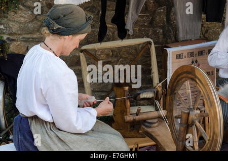 Demonstration of spinning wool by a lady in traditional Breton costume - Stock Photo