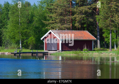 Red wooden boathouse along lake Siljan in summer, Dalarna, Sweden - Stock Photo