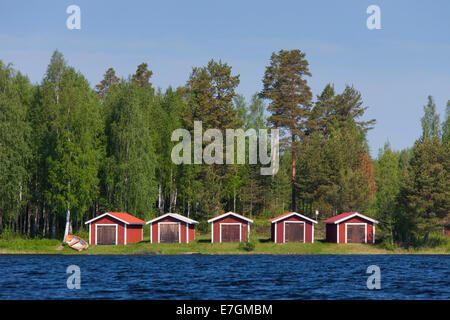 Red wooden boathouses along lake Siljan in summer, Dalarna, Sweden - Stock Photo