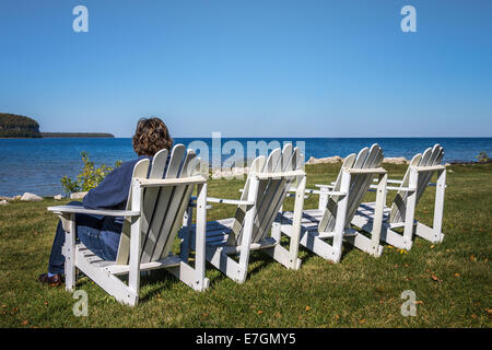 Lady sitting in one of four beach chairs in the Autumn looking at the horizon. Shot in Door County, Wisconsin. Copy - Stock Photo