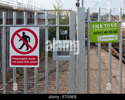 Two restriction signs on a gate at end of railway platform. One saying do not cross the other offering help from - Stock Photo