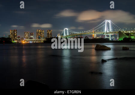 Tokyo Rainbow Bridge and skyline night view from Odaiba island - Stock Photo