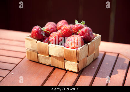 Fresh strawberry in basket on wooden table background - Stock Photo