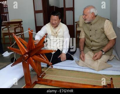 New Dehli, India. 17th Sep, 2014. Chinese President Xi Jinping (L) rotates a spinning wheel that was once used by - Stock Photo