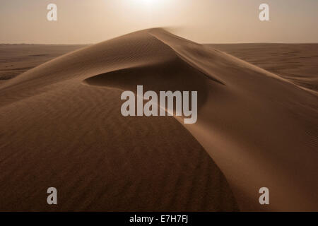 Desert winds shift the sands atop a sand dune in the middle of the Rub' al Khali desert in Saudi Arabia. - Stock Photo
