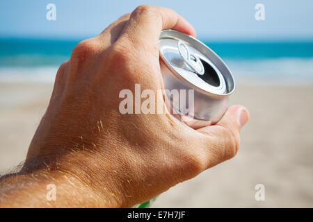 Aluminum can of beer in a male hand with beach and sea on background - Stock Photo