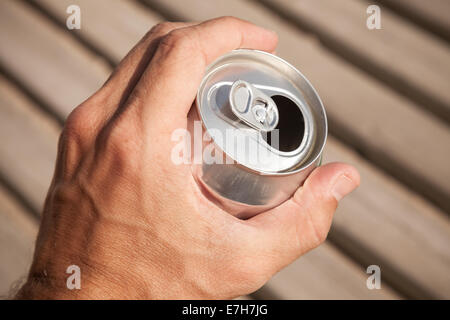 Aluminum can of beer in a male hand, summer outdoor photo - Stock Photo