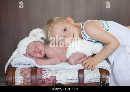 Adorable little baby boy, sleeping, his big sister cuddling him - Stock Photo