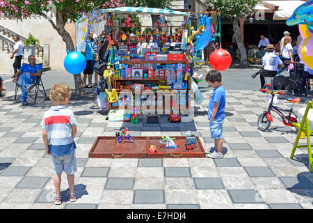 Children mesmerised by display of moving toys beside a stall in Taormina main square Province of Messina Sicily - Stock Photo