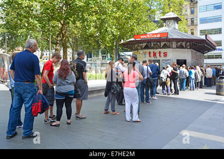 Queue of people waiting to buy theatre tickets from sales booth operated by Society of London Theatre - Stock Photo