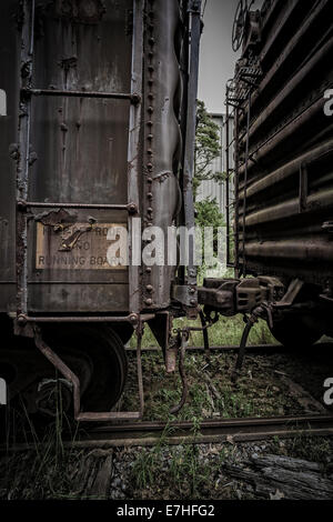 A dark and grungy industrial scene with old rusty train cars coupled and a ladder leading to the roof. - Stock Photo