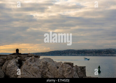 Solitary man watches the sunset over the Baie des Anges in Nice, France - Stock Photo