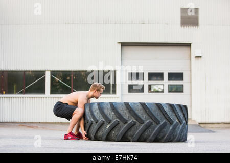 Determined Athlete Lifting Large Tire - Stock Photo