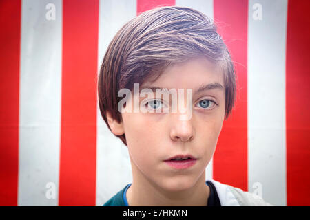 portrait of a handsome teenager boy in front of a red and white striped background - Stock Photo