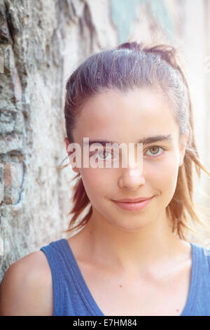portrait of a beautiful teenager girl leaning against a wall. - Stock Photo