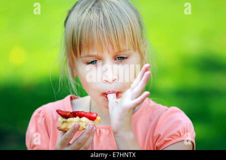Portrait a young girl eating a tasty cake - Stock Photo