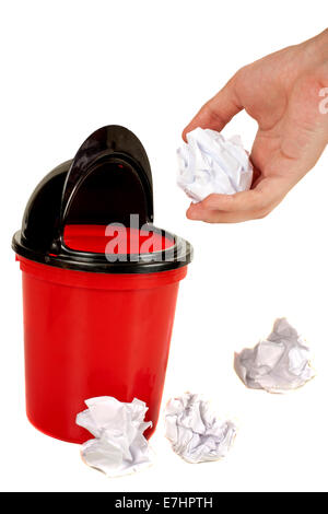 Hand placing paper in trash and some other crumpled paper balls - Stock Photo