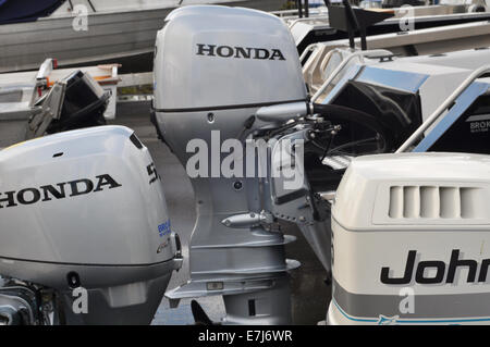 Various outboard engines on transoms of recreational vessels in boat yard ready for sale - Stock Photo