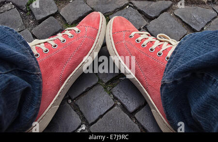 Feet in red sneakers and jeans outdoors. Making first step. - Stock Photo