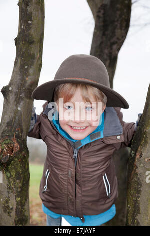 High-spirited boy, 5, wearing a hat, on a tree - Stock Photo