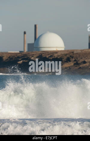 Wave crashing ashore with Dounreay Nuclear facility behind, Scotland - Stock Photo