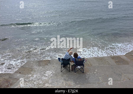 A couple sit by the sea in Falmouth, Cornwall taking a 'selfie' - Stock Photo