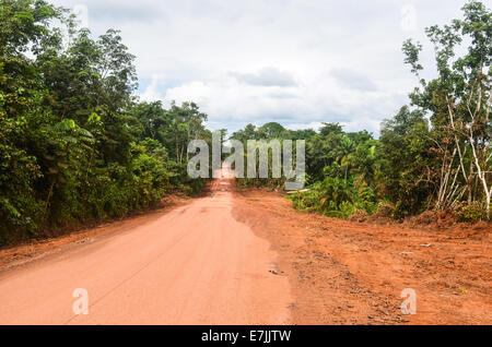Red earth mud road in Liberia, Africa - Stock Photo