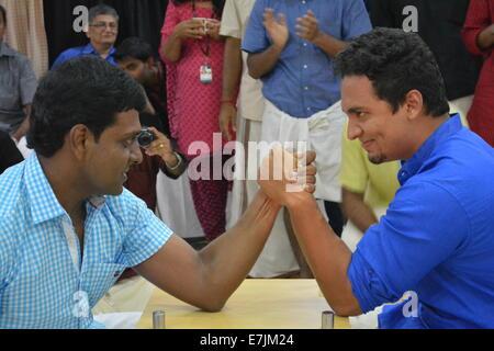 Arm wrestling between Indian men in office - Stock Photo