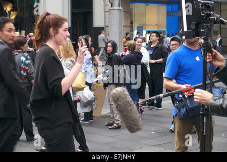 Sydney, Australia. 19th September, 2014. Young person showing off their new iphone 6 whilst being interviewed by - Stock Photo