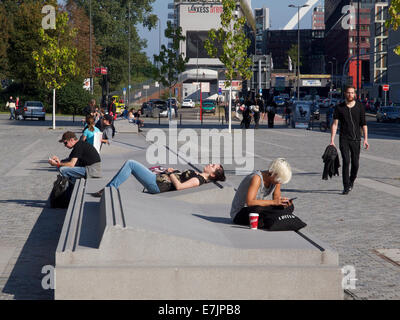 Concrete street furniture with young people relaxing in the sun and using mobile phones at Cologne train station, - Stock Photo