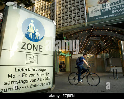 Pedestrian zone sign in the city center of Cologne, NRW, Germany, with bicyclist passing - Stock Photo