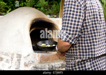 earth clay cob oven.  Now the oven has been built its time to start cooking.  The first dish of herb potatoes to - Stock Photo