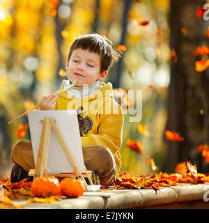 Cute little boy painting in golden autumn park on beautiful autumn day - Stock Photo