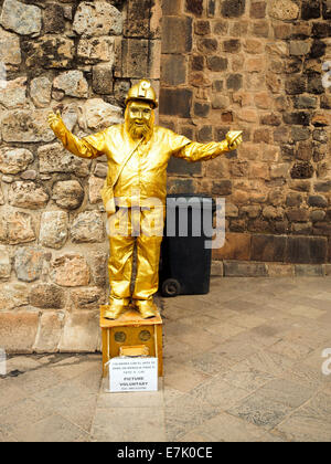 Human statue street performer in golden clothes - Cusco, Peru - Stock Photo